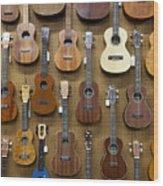 Various Guitars & Ukuleles Hanging From Wall Wood Print