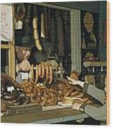 Vendor Holds Up Sausages For Young Girl Wood Print