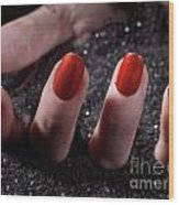 Woman Hand With Red Nail Polish Buried In Black Sand Wood Print