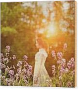 Woman Staning Sideways In Garden At Sunset Wood Print