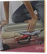 Woman Trying To Close Overflowed Suitcase On Bed Wood Print