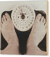 Woman's Feet On A Set Of Weighing Scales Wood Print