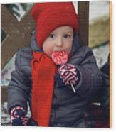 Baby In Red Hat Sits On A Bench In The Street With Candy Wood Print