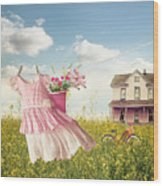 Child's Dress And Toys Hanging On Line With Farmhouse In Backgro Wood Print