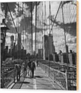 people walking over the brooklyn bridge between cables towards lower manhattan New York City USA Wood Print