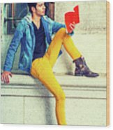 Young Man Reading Red Book, Sitting On Street Wood Print
