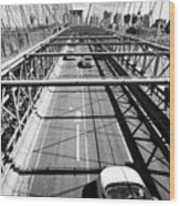 traffic vehicles driving over the worn tarmac on brooklyn bridge New York City USA Wood Print