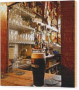 A Pint Of Dark Beer Sits In A Pub Wood Print by Jim Richardson