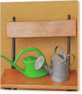 A Watering Can Of  Aluminium And A Plastic One Laid On Wooden Bench Wood Print