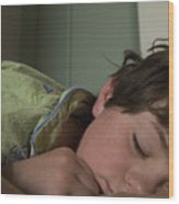 A Young Boy Sleeps In Green Pajamas Wood Print