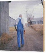 An Elderly Farmer In Overalls Walks Wood Print