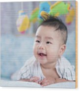 Asian Newborn Baby Smile In A Bed With Fish And Animal Mobile Wood Print