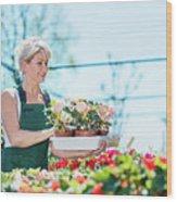 Attractive Gardener Selecting Flowers In A Gardening Center. Wood Print