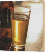 Backlit Glass Of Beer And Empty Bottle On Table Wood Print