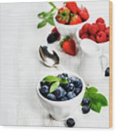 Berries In Bowls  On Wooden Background. Wood Print