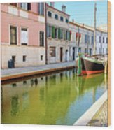 boat in a canal of the colorful italian village of Comacchio in  Wood Print