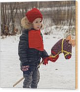 Boy On A Toy Horse Is Standing On The Street In Winter Wood Print