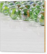 Composition With Green Marbles On White Background Wood Print