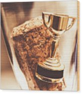 Cork And Trophy Floating In Champagne Flute Wood Print