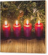 Glowing Red Candles With Snow Covered Evergreen Branch On Rustic Wood Print