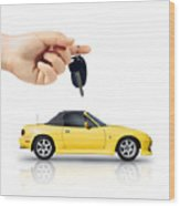 Hand Holding Key To Yellow Sports Car Wood Print