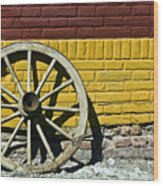 Old Wooden Wheel Against A Wall Wood Print