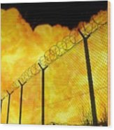 Realistic Orange Fire Explosion Behind Restricted Area Barbed Wire Fence, Blurred Background Wood Print