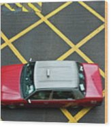 Red Taxi Cab Driving Over Yellow Lines In Hong Kong Wood Print