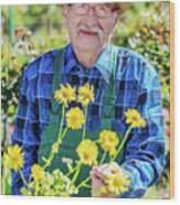 Senior Gardener Showing A Potted Flower. Wood Print