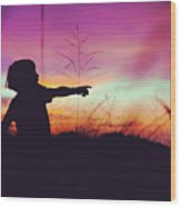 Silhouette Of A Playful Boy Pointing With Finger In The Field During Beautiful Sunset Wood Print