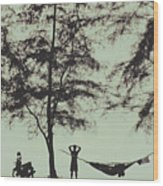 Silhouette Of A Young Men With Crossed Hands Above His Head Camping Hammocking In The Nature Wood Print