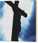 Silhouetted Crucifix Against A Cloudy Sky Wood Print