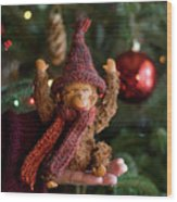 Silly Old Monkey Toy In A Child Hands Under The Christmas Tree Wood Print