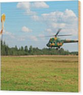 The Helicopter Over A Green Airfield. Wood Print