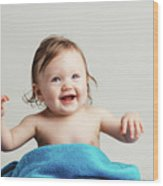 Toddler With A Cozy Blanket Sitting And Smiling. Wood Print