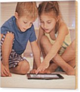 Two Happy Children Playing On The Tablet Wood Print