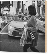 woman crossing crosswalk in front of yellow cabs in the evening in Times Square New York City USA Wood Print