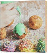 Woman's Hand Coating A Donut With Green Frosting. Wood Print