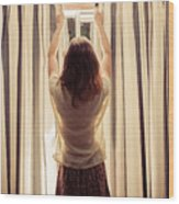 A Young Woman Is Opening The Curtains Wood Print