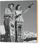 Couple Holding Snowshoes, Woman Pointing Wood Print