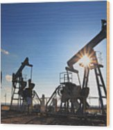 Working Oil Pumps Silhouette Against Sun Wood Print