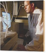A Caucasian Chemist Analyzes Data On A Computer Screen While Standing In A Laboratory Wood Print