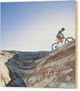 A man riding a mountain bike on an extreme sandstone ledge Wood Print