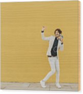 Businessman singing and dancing in front of yellow wall listening music with headphones and smartphone Wood Print