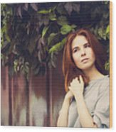 Caucasian woman standing under leaves by fence Wood Print