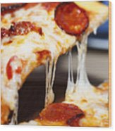 Closeup of a piece of pepperoni pizza. Italian pizza. Wood Print