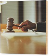 Male judge striking gavel in courtroom, close-up Wood Print