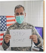 Senior military soldier holding paper with message stay home Wood Print