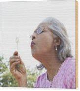 Senior woman blowing bubbles Wood Print