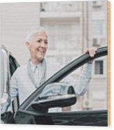 Senior Woman Smiling While Entering A Car Wood Print
